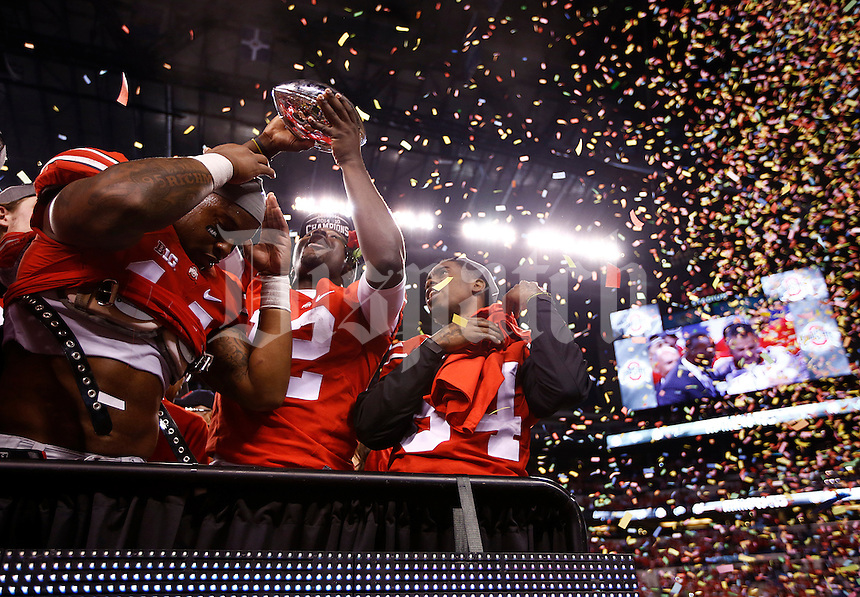 Ohio State Buckeyes quarterback Cardale Jones (12) hoists the trophy after the Big Ten Championship game between the Ohio State Buckeyes and the Wisconsin Badgers at Lucas Oil Stadium in Indianapolis, Sunday night, December 7, 2014. The Ohio State Buckeyes defeated the Wisconsin Badgers 59 - 0 to become Big Ten Champions(The Columbus Dispatch / Eamon Queeney)