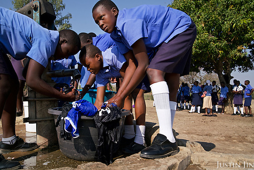 Children at a secondary School in drought-hit Masvingo Province, Zimbabwe, wash clothes by a borehole.  <br /> <br /> Drought in southern Africa is devastating communities in Zimbabwe, leaving 4 million people urgently in need of food aid. The government declared a state of emergency,. <br /> <br /> Here in Masvingo Province, the country's hardest hit province, vegetation has wilted, livestock is dying, and people are at serious risk of famine. <br /> <br /> Pictures shot by Justin Jin