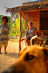 Group of people with a dog in a fishermen village at.Panasia Island.Panasia is a spectacular island of uplifted coral reef making jagged limestone cliffs in the Louisiade Archipelago..The Louisiade Archipelago is a string of ten larger volcanic islands frequently fringed by coral reefs, and 90 smaller coral islands located 200 km southeast of New Guinea, stretching over more than 160 km and spread over an ocean area of 26,000 km  between the Solomon Sea to the north and the Coral Sea to the south. The aggregate land area of the islands is about 1,790 kmu178  (690 square miles), with Vanatinai (formerly Sudest or Tagula as named by European claimants on Western maps) being the largest..Sideia Island and Basilaki Island lie closest to New Guinea, while Misima, Vanatinai, and Rossel islands lie further east..The archipelago is divided into the Local Level Government (LLG) areas Louisiade Rural (western part, with Misima), and Yaleyamba (western part, with Rossell and Tagula islands. The LLG areas are part of Samarai-Murua District district of Milne Bay. The seat of the Louisiade Rural LLG is Bwagaoia on Misima Island, the population center of the archipelago. .The Louisiade Archipalego is part of the Milne Bay province of Papua New Guinea..It lies between approximately 10 degrees south and 11.5 degrees south, and 151 degrees east and 154 degrees east. It is an area of Islands, reefs and cays some 200 nm long and 50 nm wide, stretching from the south east tip of mainland Papua New Guinea in a east south east direction..Panasia Island.Panasia is a spectacular island of uplifted coral reef making jagged limestone cliffs in the the Louisiade Archipelago..The Louisiade Archipelago is a string of ten larger volcanic islands frequently fringed by coral reefs, and 90 smaller coral islands located 200 km southeast of New Guinea, stretching over more than 160 km and spread over an ocean area of 26,000 km  between the Solomon Sea to the north and the Coral Sea to the south. The a