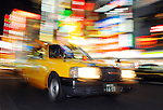 A taxi drives through a busy downtown district of Tokyo. Photographer: Robert Gilhooly.