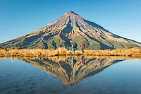 Hikers under Taranaki, Mt. Egmont with reflections in alpine tarn, Egmont National Park, North Island, New Zealand, NZ