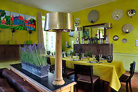 A contemporary triptych in vibrant colours depicting the chateau hangs on one wall of the lime-green dining room