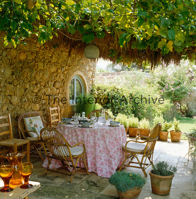 Wicker chairs surround a table laid for lunch on a terrace shaded by a vine-covered arbour