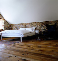 A contemporary bed stands on a pine floor of wide planks against a rough stone wall