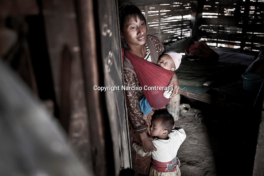 Kachin family stand up at the entrance of a wood hut used as dormitory. The hut is part of a KIA outpost up to the high mountains of the Maija Yang front line.