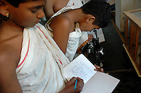 A student of Om Shantidhama using a microscope during a biology practical class.  Om Shantidhama is a residential vedic school for boys. Nestled among the confluence of hills, forest and rivers - Om Shanti Dhama is a world removed from the maddeningly fast and often chaotic urban India. Students from allover the country are selected to take part in its Vedic and free education system. What is unique about this institute is that they have blended the traditional and modern education system. Here computer and science is taught with the same passion as the Vedas and Shastras, helping the students to grow spiritually as well as earn a living. Bonding with the nature and animal world is a mandatory part of the institute's curriculum. Karnataka, India. Arindam Mukherjee