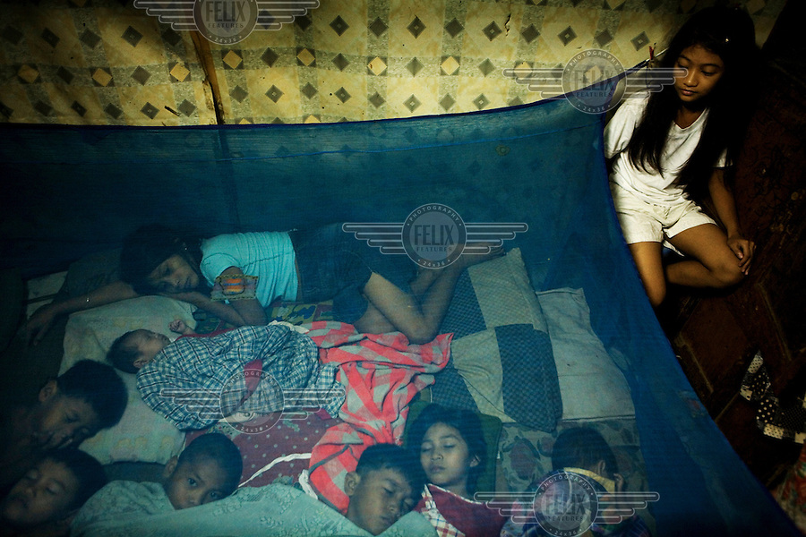 The Esponilla family sleep in their house in Santo Nino, Manila. Bhona and Charito Esponilla have seven children and live in 20 square meters of space. Poverty and overpopulation are closely connected. Poor families often have the most children. People in this area live in small homemade huts, many made entirely from rubbish and leftover building materials that they found on the nearby garbage dump. These houses are all illegal, since no one has the acquired permissions to live on the land. People have been living here for up to twenty years - but everyday they might get moved and their neighbourhood demolished to make room for new apartment blocks that they could never afford to buy.