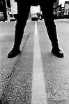 Female legs stand on either side of a painted line which marks the spot were the former Berlin Wall used to divide East and West Berlin, Germany.