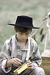 A young boy in period clothes playing domino games at a Civil War Reenactment at the Wade House Greenbush Wisconsin