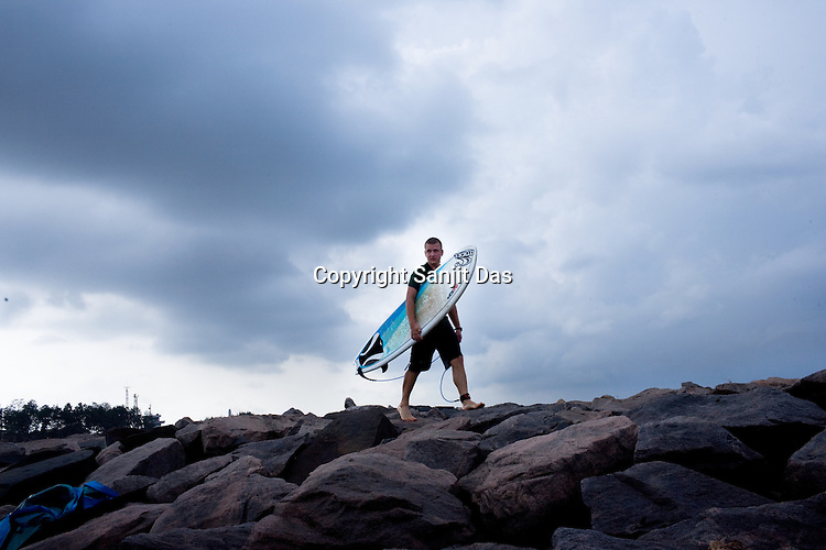"""Gaura Gopal, one of the Krishna devotees from the Kaliya Mardana Krishna Ashram is seen walking on the rock jetty of the Arabian Sea on the beach front of Mangalore, Karnataka, India.  ..Krishna devotees in the Gaudiya Vaishnava tradition of Hinduism, they are known collectively as the """"surfing swamis."""" The """"surfing ashram"""" is growing in popularity and surfing here is a form of meditation, a spiritual practice leading to heightened states of awareness."""