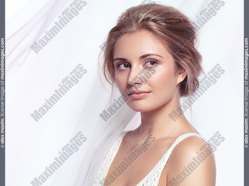 Pretty young woman face with clean natural look on light flowy fabric background