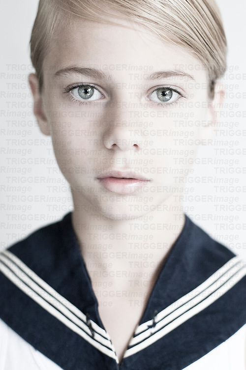Male youth with blonde hair wearing naval shirt looking at camera