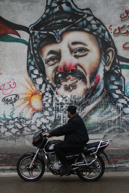 A Palestinian man rides his motorcycle passes by a mural of the Palestinian Leader Yasser Arafat, in Gaza City on January 1, 2011. Palestinians celebrating the 46th anniversary of the founding of the Palestinian National Liberation Movement (Fatah). Photo by Ashraf Amra