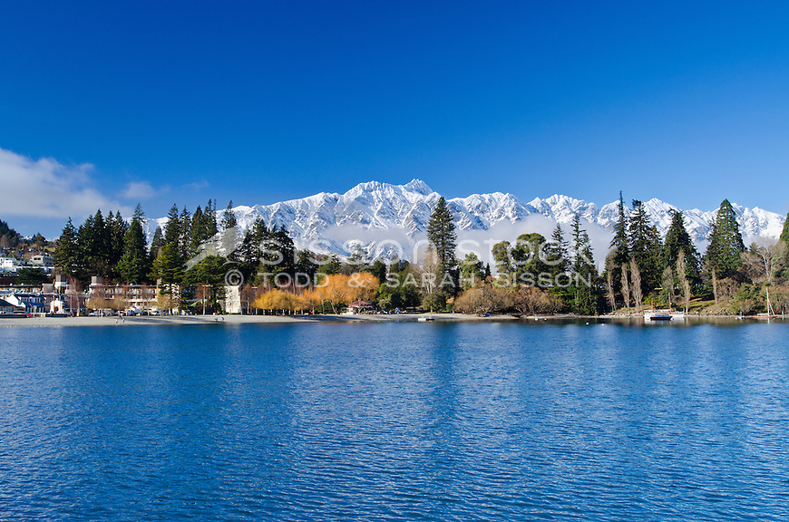 Snow covered Remarkables mountains rise above cloud. Queenstown Gardens in the foreground, South Island, New Zealand