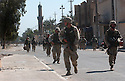 U.S. Army soldiers  move through a street in front of the al-Baya'a mosque in Baghdad, Iraq during an October 07, 2003  protest there against the detention of local Shia Imam Mo'ayed al-Khezragi by the U.S. military .
