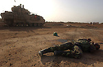 U.S. Army 3rd Division soldiers roll past the body of a slain Iraqi soldier April 4, 2003 after an assault on the Baghdad International Airport. U.S. and Iraqi forces exchanged heavy fire throughout the day as they battled for control of the strategic facility.
