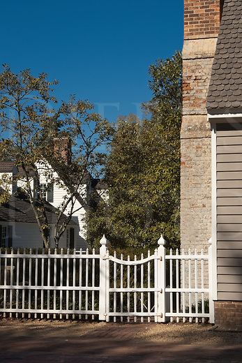 A white picket fence and closed side gate in Colonial Williamsburg, VA, USA.