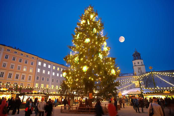 Christmas market stalls and Christmas tree at night  at Satlzburgh market - Austria