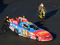 Sep 19, 2015; Concord, NC, USA; NHRA funny car driver John Force and daughter Courtney Force ride a scooter alongside his Jeff Gordon tribute paint scheme car during qualifying for the Carolina Nationals at zMax Dragway. Mandatory Credit: Mark J. Rebilas-USA TODAY Sports