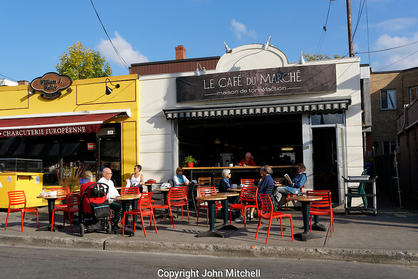 People sitting at tables outside the The Cafe de la Marche next to the Jean Talon Market, Montreal Quebec, Canada