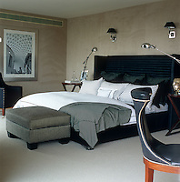 Black and white bed linen in constrasting checks and stripes make an interesting statement against the grey faux-suede walls of this London bedroom