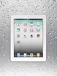 White Apple iPad 2 tablet computer with desktop icons on its display on wet gray steel background