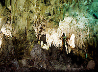 LIMESTONE CAVERN<br /> Stalactites and Stalagmites in Limestone Cavern<br /> Calcium carbonate deposits (Stalactites) hang from the top of limestone caverns, formed by the dripping of mineralized solutions. Corresponding columnar deposits (Stalagmites) are built upward. Papoose Room, Carlsbad.