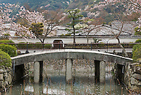 A simple curved stone bridge crosses one of the ornamental lakes in the 14th century Zen garden at Tenryu-ji Temple, Kyoto