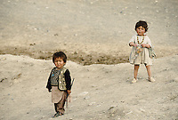 Two Childs living next to the giant Buddha in the Bamiyan valley.