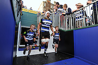 Dave Attwood of Bath Rugby, mascots in hand, leads his team out onto the field. West Country Challenge Cup match, between Bath Rugby and Gloucester Rugby on September 26, 2015 at the Recreation Ground in Bath, England. Photo by: Patrick Khachfe / Onside Images