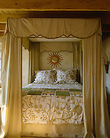 This four-poster bed has checked yellow silk curtains, an American Indian patchwork quilt and an embroidered bedcover