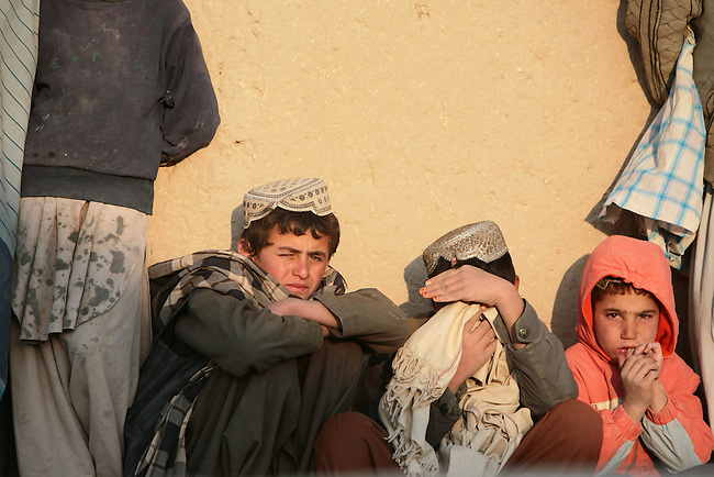 Three boys sit against a wall amid a group of men who've gathered to watch U.S. soldiers and Afghan troops search their village for Taliban fighters and weapons in the Shah Joy district of Zabul province, Afghanistan. Oct. 26, 2010. DREW BROWN/STARS AND STRIPES