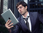 Portrait of a businessman using Apple iPad tablet computer in city downtown with office buildings in the background. Toronto, Ontario, Canada.