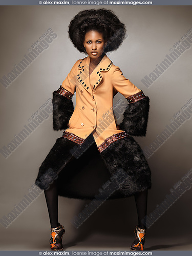 High fashion photo of a young woman wearing a coat with black fur