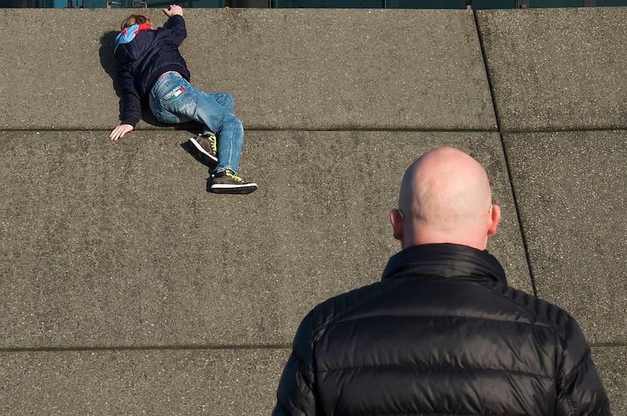 Nederland, Rotterdam, 12 jan 2014<br /> Kop van Zuid. Vader en zoon. Vader kijkt toe hoe zijn zoontje een muurtje beklimt.<br /> <br /> Foto: Michiel Wijnbergh