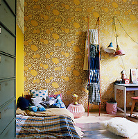 The bedroom has a relaxed, informal feel with its yellow patterned walls and simple low bed