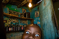 A Haitian boy tries to sell a bottle of soft drink inside the house in the slum of Cité Soleil, Port-au-Prince, Haiti, 24 July 2008. Cité Soleil is considered one of the worst slums in the Americas, most of its 300.000 residents live in extreme poverty. Children and single mothers predominate in the population. Social and living conditions in the slum are a human tragedy. There is no running water, no sewers and no electricity. Public services virtually do not exist - there are no stores, no hospitals or schools, no urban infrastructure. In spite of this fact, a rent must be payed even in all shacks made from rusty metal sheets. Infectious diseases are widely spread as garbage disposal does not exist in Cité Soleil. Violence is common, armed gangs operate throughout the slum.