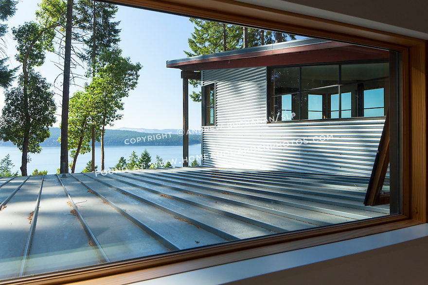 A window looking out to the Salish Sea across the metal roof of a contemporary island home. This image is available through an alternate architectural stock image agency, Collinstock located here: http://www.collinstock.com