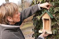 Vogel-Futterhäuschen wird von Frau an einem Baum befestigt, Futterhaus, Futterhäuschen, Vogelfutter