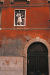 Statue ensconced in wall of building next to a canal in Venice, Italy.
