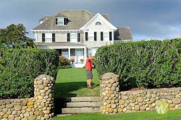 Cape Cod styled home, Chatham, MA. Shore Drive. Man trimming hedge.