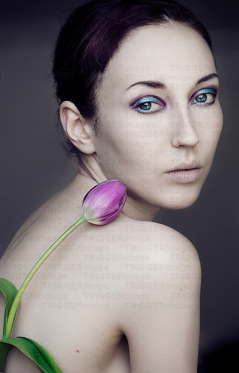 Young girl with combed back dark hair and colourful make up and pale skin, looking over her shoulder with a tulip held to her back, with simple background.