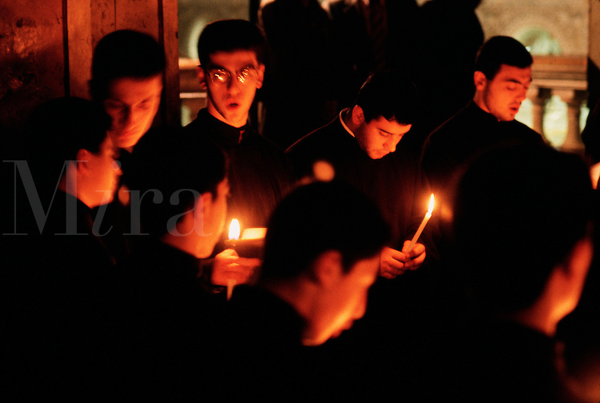 Alterboys at the Armenian Orthodox Church of the Sepulchre hols clandels as they serve mass. Jerusalem, Israel.