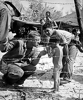 Marines try to soothe a crying child by offering a shiny rations tin.  Children are sheltered with their families in a camp set up for refugees from battle areas by U.S. Marine Civil Affairs authorities on Saipan.  July 1944.  PhoM1c. Ted Needham.  (Coast Guard)<br /> Exact Date Shot Unknown<br /> NARA FILE #:  026-G-2528<br /> WAR &amp; CONFLICT BOOK #:  1268