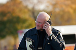 A police detective listening to the radio at his ear.