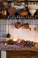 In this rustic kitchen a stone sink is filled with freshly picked sprigs of holly and winter berries