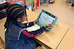 Oakland CA Developmentally disabled girl working with AAC (alternative augmentative communnication) device to learn how to read in special education classroom   MR