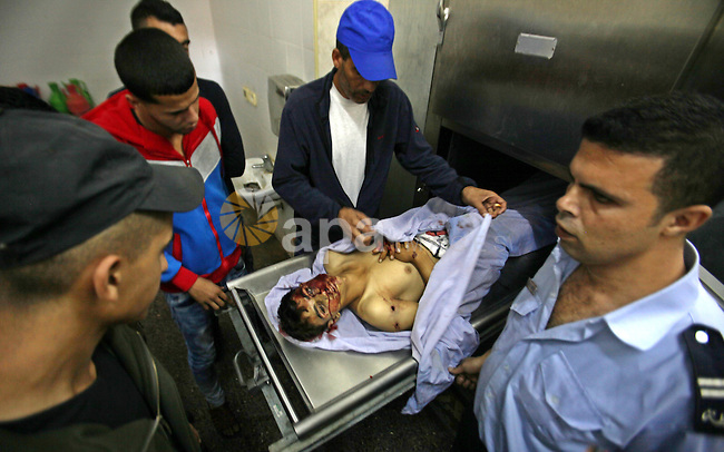 Palestinians arroud the body of Mahmoud Nazzal,18, in a hospital who was killed  at the Jalama checkpoint near Jenin, West Bank, Saturday, Oct. 31, 2015, after he was killed at the al-Jalama checkpoint by Israeli security forces reportedly before he could attack them. It was the latest shooting of a suspected Palestinian attacker since the start of unrest in early October that has triggered fears of a third Palestinian intifada, or uprising, against Israel. Photo by Nedal Eshtayah