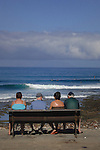 Four people sitting on a bench seat watching the surfers and  waves, Playa de las Americas,Tenerife, Canary Islands.