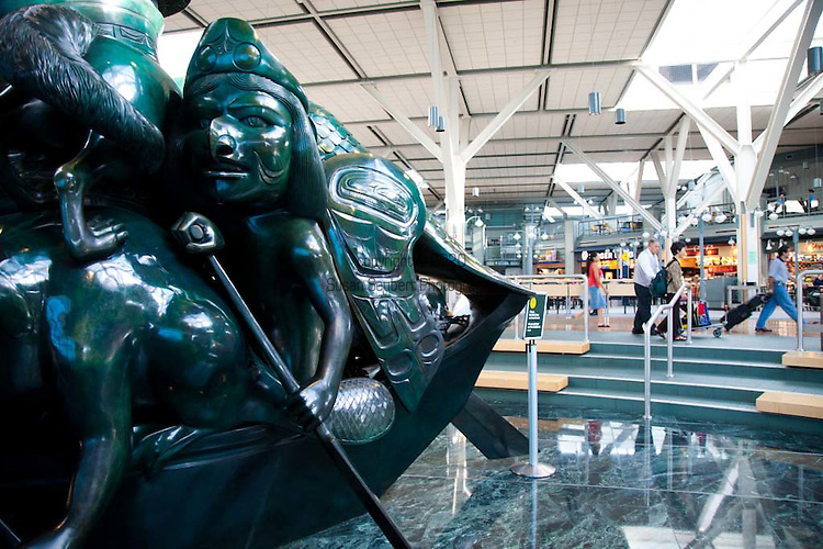 YVR, Vancouver, B.C. International Airport.  The interior design of the International Terminal was inspired by British Columbia's great outdoors and the art of the Northwest Coast that depicts British Columbia's native wildlife, mountains, rivers, forests, and aboriginal heritage. .The Spirit of Haida Gwaii, The Jade Canoe, by Bill Reid, provides the focal point to the entrance of the International Terminal. The bronze sculpture features legendary Haida creatures paddling a boat that &quot;goes on, forever anchored in the same place.&quot;